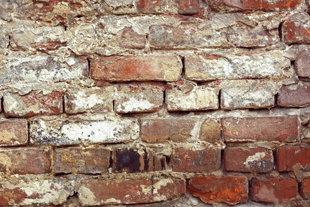 outmoded: Detail of old brick wall with shelled color paint layers Stock Photo