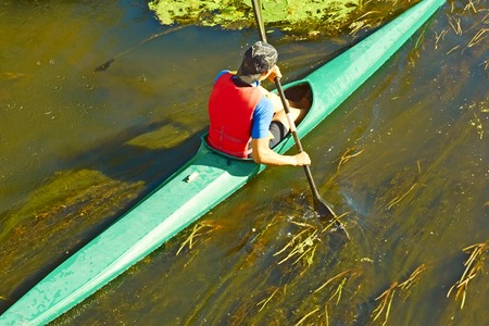 canoeist: Canoeist in a canoe floating on the river overgrown with algae in a sunny day, the view from above