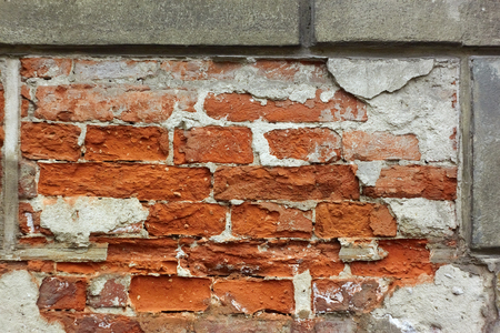 Fragment of old brick wall with plaster shelled photo