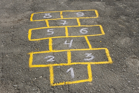 Figures in childish game hopscotch painted with yellow paint on asphalt photo