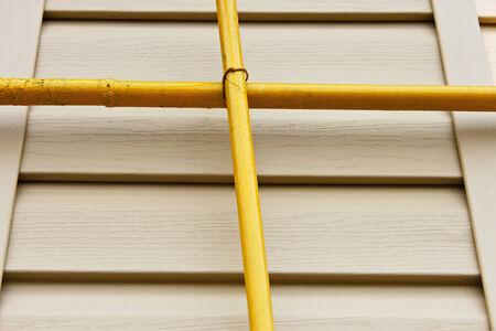 perpendicular: Due tubi del gas gialle perpendicolari tra loro su uno sfondo di un muro coperto di rivestimenti beige