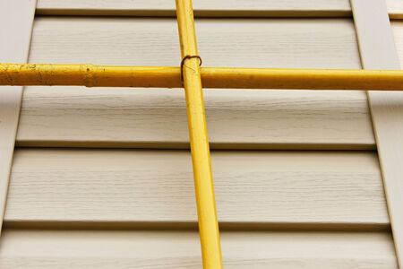 perpendicular: Two mutually perpendicular yellow gas pipes on a background of a wall covered with beige siding