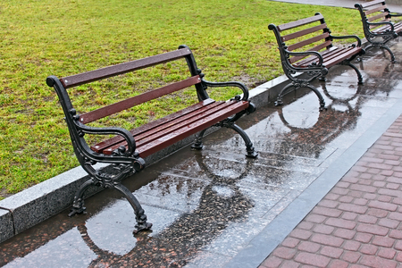 wetness: Row of wet benches after the rain in the city square in Lviv, Ukraine