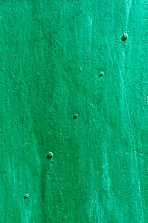 aircraft rivets: Metal sheet with rivets along the diagonal painted in green and turquoise color in bright sunlight Stock Photo
