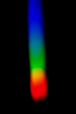 結果としてカラフルなスペクトルを持つ暗い画面が三角プリズムで白色の太陽光を分散させる