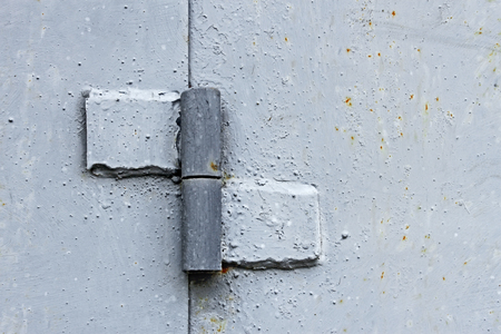 Welded: Metal hinge welded to the two steel plates, painted in light gray color, close-up