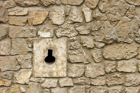 fastness: Loophole in medieval masonry stone fortress close-up in Lviv, Ukraine