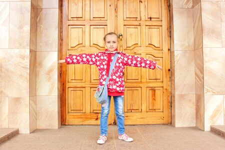 Beautiful small schoolgirl standing with widely outstretched hands before big wooden door