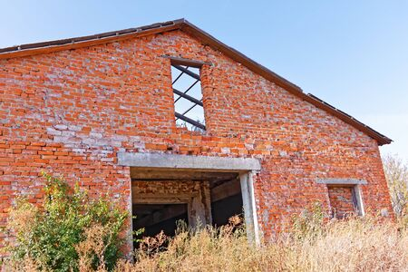 uncouth: Old abandoned break barn with destroyed parts on the background of blue sky in serene autumn day