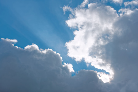 climatic: Heaven, cloudscape of light white and gray clouds against blue sky with sun beams Stock Photo