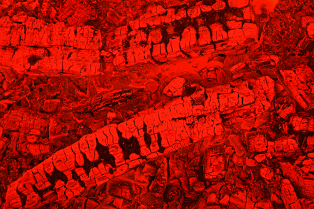 Firewood background with smoldering charcoal embers in red color, top view