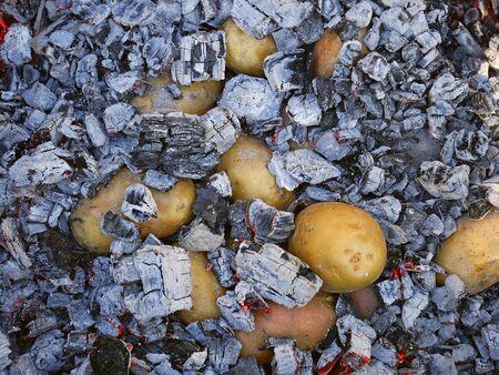 Les tubercules de pommes de terre cuits dans le charbon de bois chaud avec des braises de bois chauffées au rouge, vue de dessus