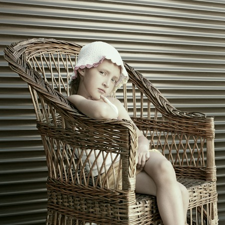 Beautiful small Caucasian girl seating in a large wicker chair, edited as a vintage photo in coffee color