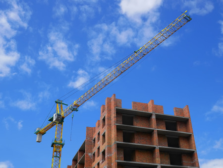Residential brick building construction with crane on the background of blue sky Stock Photo