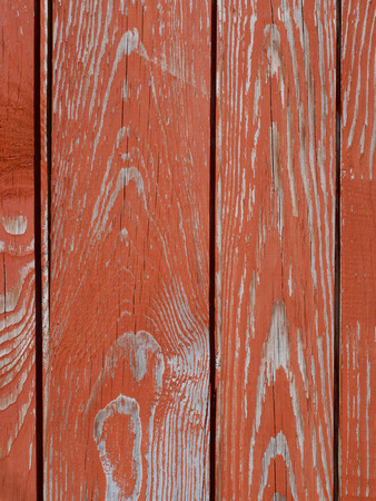 Fragment of old wooden fence with peeling red paint