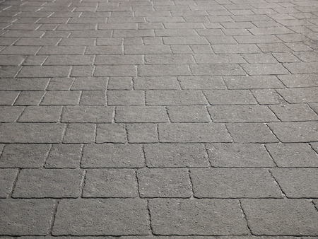 Gray wet concrete pavement slabs in sunlight