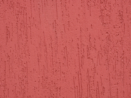Detail of dark pink painted bumpy ornamental wall stucco covering, close-up