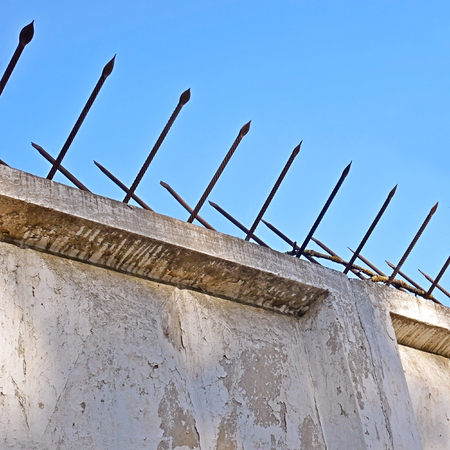 High old concrete fence with two-sided sharp iron pins against a blue cloudless sky Stock Photo