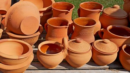 Lots of red and orange clay pottery in bright sunlight, traditional Ukrainian handicraft