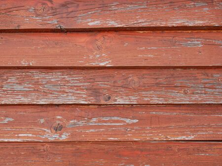Detail of old weathered wooden roof pained in red with horizontal superimposed parallel boards