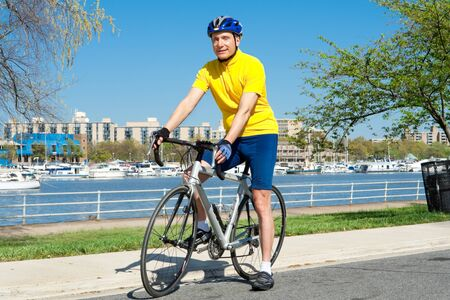 Caucasian senior man sitting on a road bike.  Hes wearing a helmet and cycling clothing.