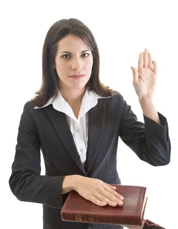 swearing: Caucasian woman looking at camera and swearing on a bible.  Isolated on white. Stock Photo