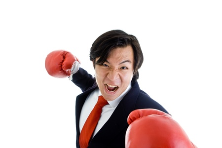 Asian businessman punching atthreatening the camera.  Isolated on white background. photo