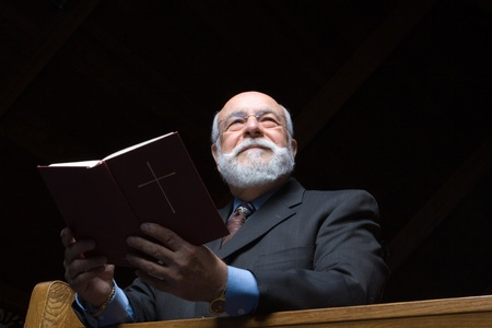 Senior man shot from below holding a hymnal  in church pew photo