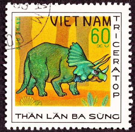 triceratops: Canceled Vietnam Vietnamese Postage Stamp Green Triceratops Dinosaur in Profile Forrest Stock Photo