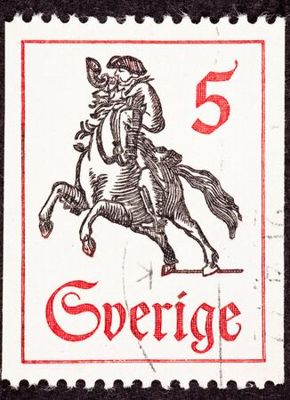 Canceled Swedish Postage Stamp Horseback Mail Delivery, Rider Blowing Postal Horn Stock Photo