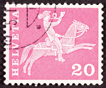 helvetia: Swiss, Switzerland, Helvetia Postage Stamp.  Man on horseback delivering mail.  Hes blowing a postal horn.  I guess it could alternatively be a fox hunt.