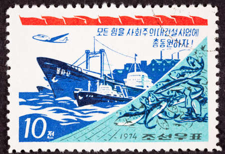 perforated: Canceled North Korean Postage Stamp regarding industrial power, shows Fishing Boat, Net, Freighter, Airplane, Factory Stock Photo