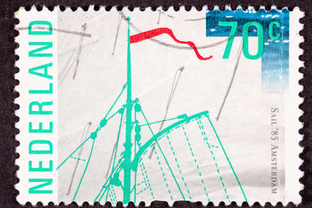Dutch Postage Stamp commemorating Sail 85 Amsterdam.  Shows top of a ships mast against a canvas sail background