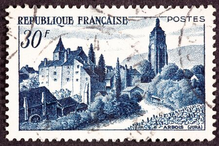 chateau: French Postage Stamp showing the Chateau Bontemps, in Arbois, Jura, France.  In the foreground is a vinyard Stock Photo