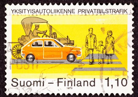 canceled: Canceled Finland Postage Stamp about Traffic Safety.  Shows family of three crossing a street at a crosswalk.  Two cars modern subcompact and a Model-T