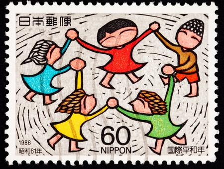 Group of people holding hands spinning in a circle. Stamp is commemorating International Peace Year. photo