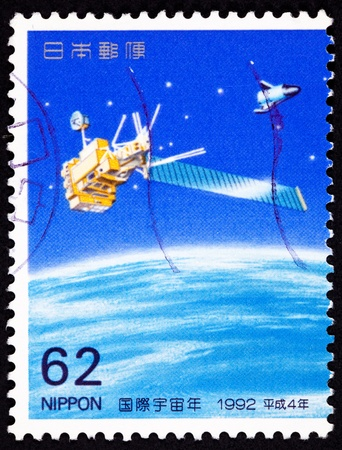 philatelic: Satellite with a solar panel and a winged spacecraft orbiting Earth.  Set of two stamps commemorating International Space Year.