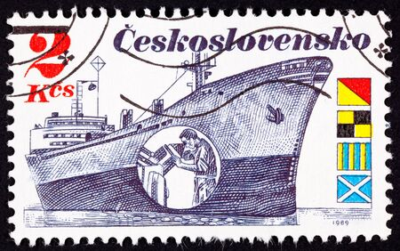 peering: Czech Freighter Brno with inset showing a man peering at radar display.  Flags spell OLGM in English. Stock Photo