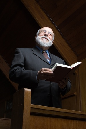 hymnal: Happy senior standing in church with a hymnal or bible.