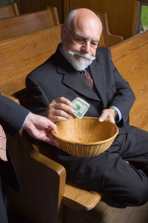 offerings: Senior man in a church putting a $20 bill in a church offering basket. Stock Photo