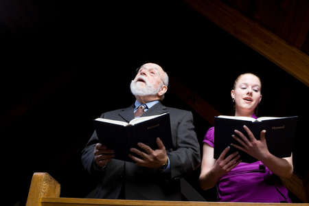 Senior man with beard and young white woman standing and singing in a church pew. photo