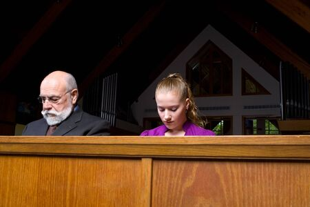 Senior man and young woman sitting and praying in a church pew. photo