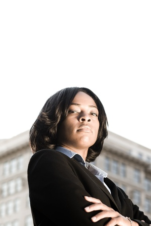 strong: Tough-Looking African American businesswoman with serious expression looking at camera.  Shot outdoors with office building and blown out sky.
