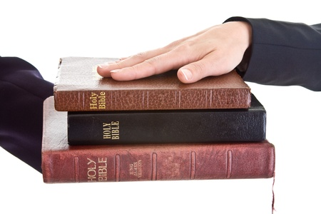 Woman's hand resting on a stack of bibles.  Swearing on a stack of bibles theme. Stock Photo - 9174370