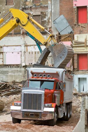 Hydraulic claw dropping rubble into dump truck at a building demolition site.