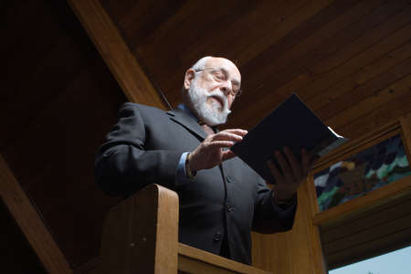 hymn: Caucasian senior man singing a hymn in church.  Shot from low angle. Stock Photo