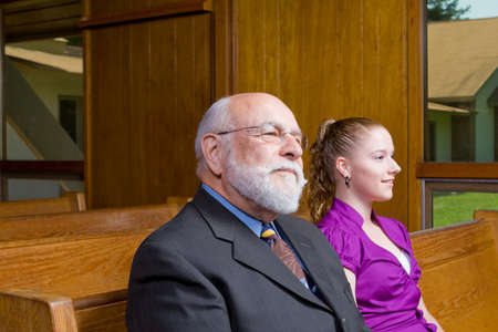 pew: Senior man and young woman sitting in a church pew Stock Photo