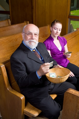 Two people passing an offering basket in church. photo