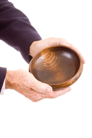 to beg: Older hands holding out a wooden bowl.