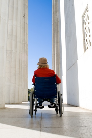 Woman in a wheelchair outside the Lincoln Memorial.  Facing away, looking toward space between columns and building. photo